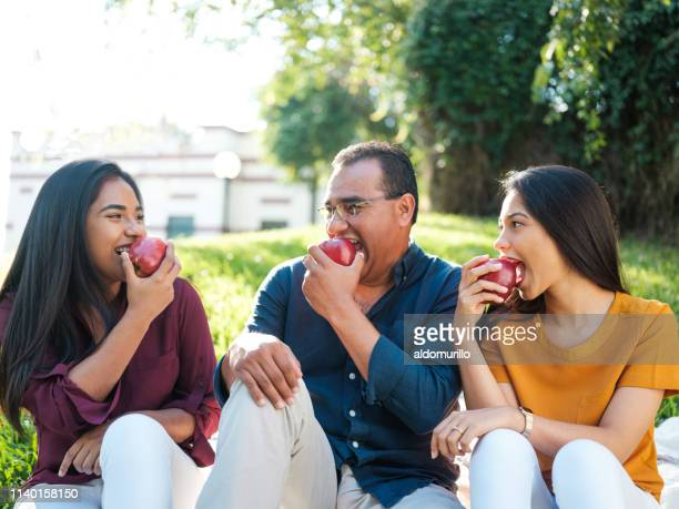 a young woman eating and apple along with her father and sister - mexican picnic stock pictures, royalty-free photos & images