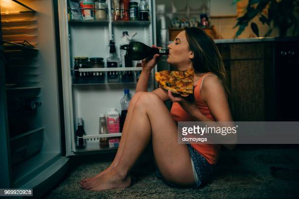 young woman eating and drinking in the kitchen late night - binge drinking stock photos and pictures