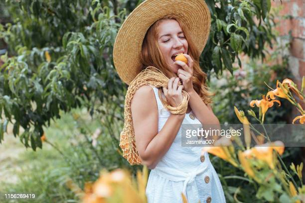 young  woman eating apricot  in garden - apricot stock pictures, royalty-free photos & images