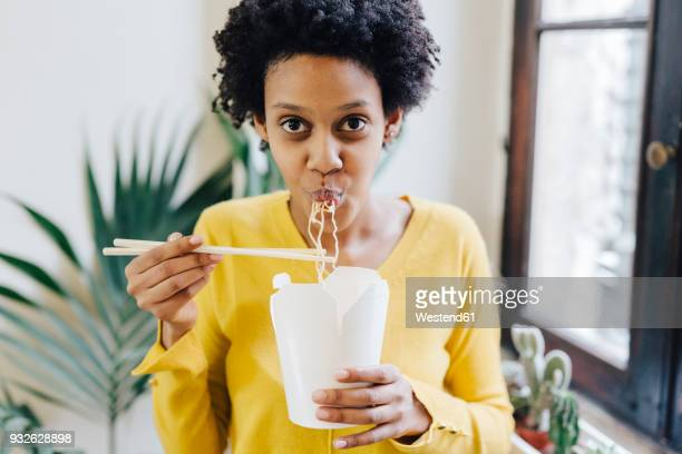 young woman eating asian noodles for lunch with chopsticks - take away food stock pictures, royalty-free photos & images