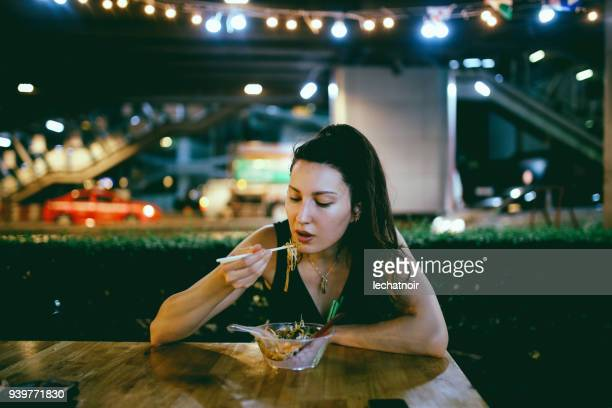 Young woman eating authentic Thai food on a street market in Bangkok, Thailand