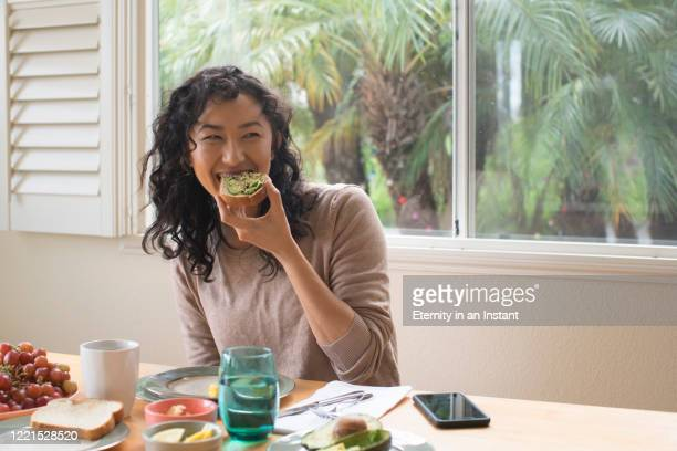 young woman eating avocado toast at home - comer - fotografias e filmes do acervo