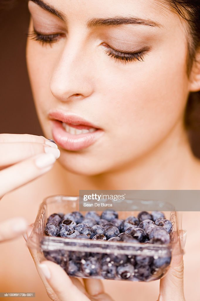 Young woman eating blue berry, close-up : Stockfoto