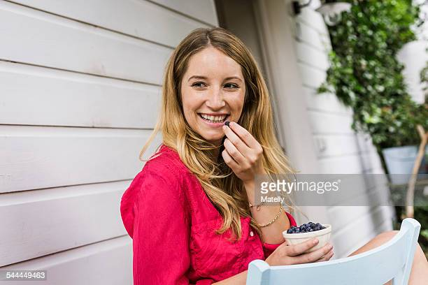young woman eating blueberries in front porch - roze bloes stockfoto's en -beelden