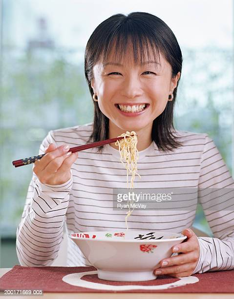 Young woman eating bowl of noodles with chopsticks, smiling, portrait