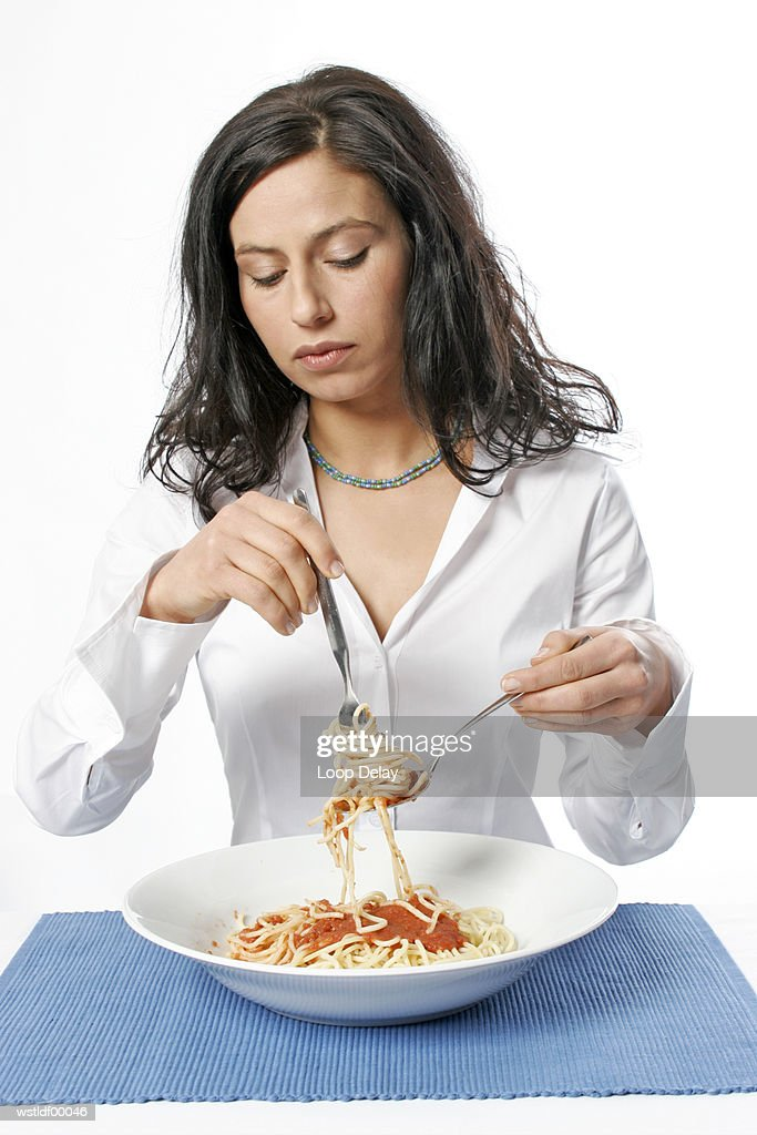 Young woman eating bowl of spaghetti with fork, portrait : Stockfoto