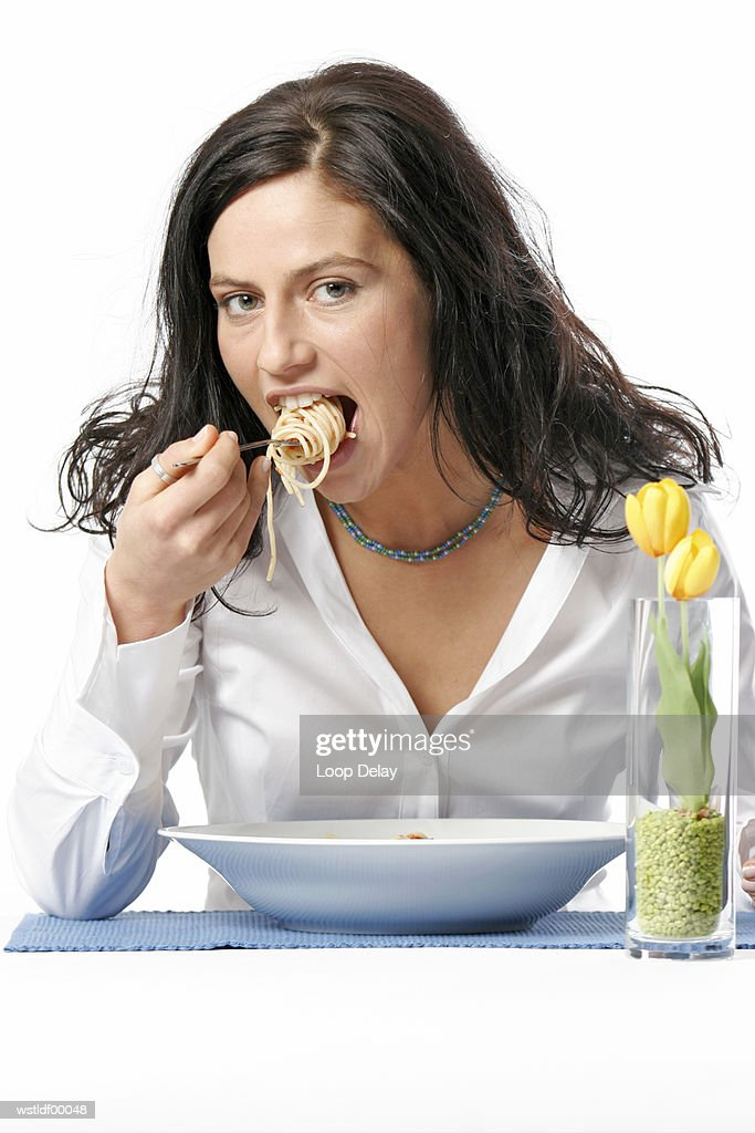 Young woman eating bowl of spaghetti with fork, portrait : Stock Photo