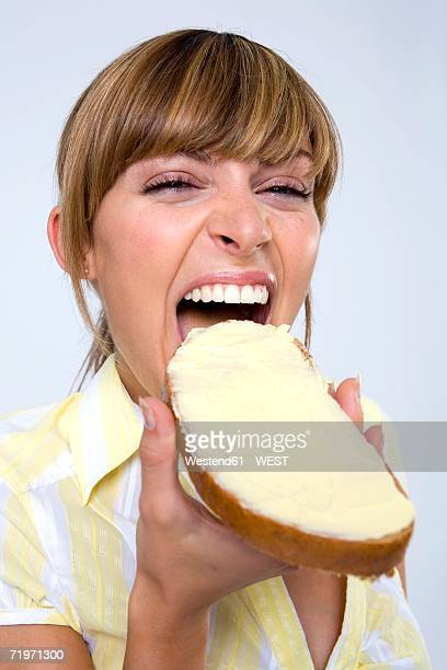 Young woman eating bread and butter, close-up