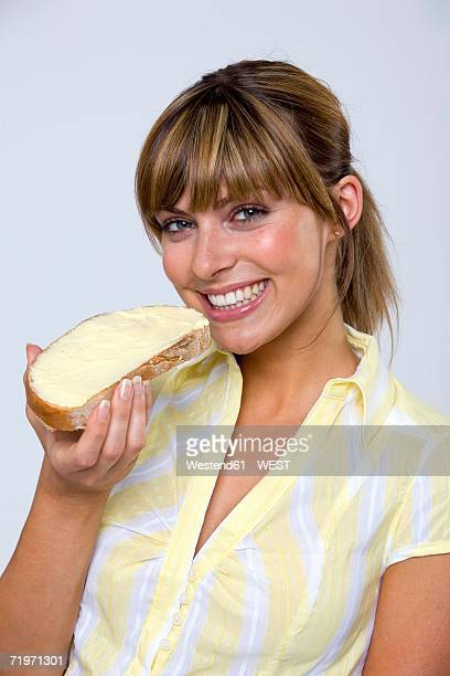 Young woman eating bread and butter, portrait, close-up