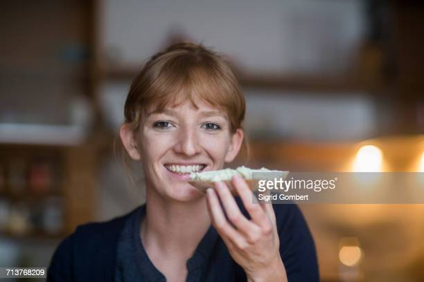 young woman eating bread with cream cheese - sigrid gombert stock pictures, royalty-free photos & images