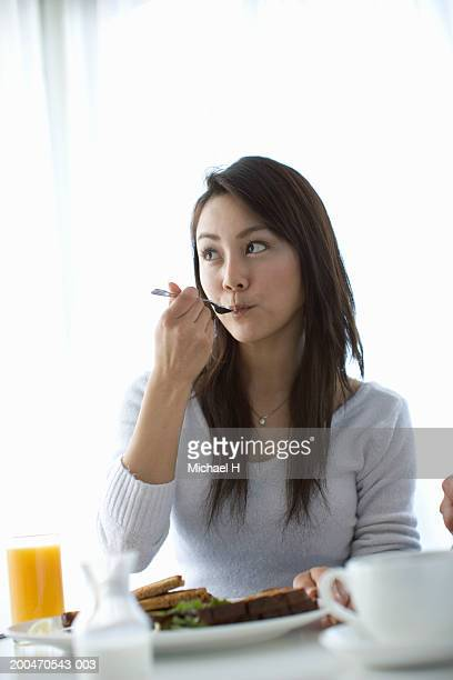 Young woman eating breakfast, looking away