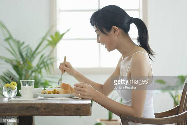 a young woman eating breakfast - camisole stock photos and pictures