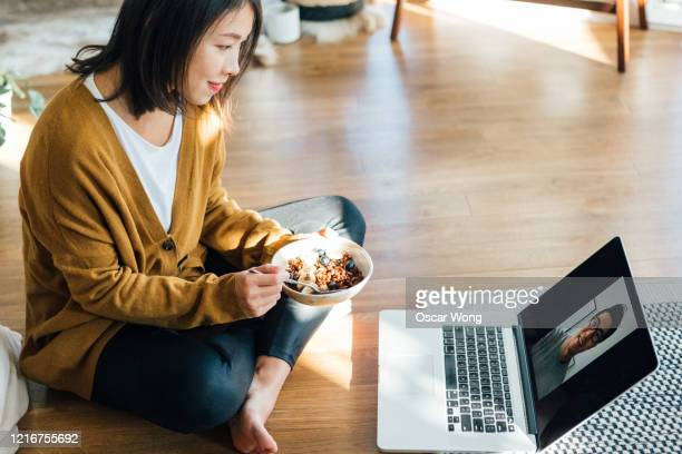 young woman eating breakfast while having a video call using laptop at home - copy space stock pictures, royalty-free photos & images