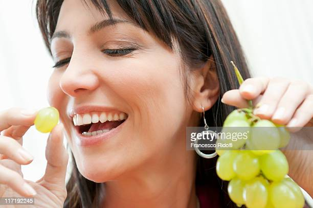 young woman eating bunch of grapes - white grape stock photos and pictures