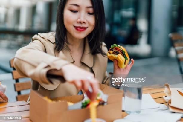 young woman eating burger and chips outdoors - restaurant stock pictures, royalty-free photos & images