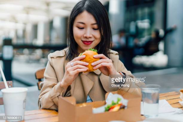 young woman eating burger and chips outdoors - snack stock pictures, royalty-free photos & images