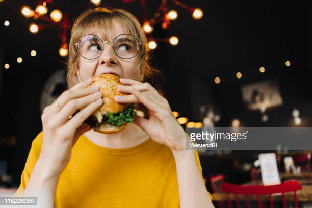 young woman eating burger in a restaurant - 噛む ストックフォトと画像