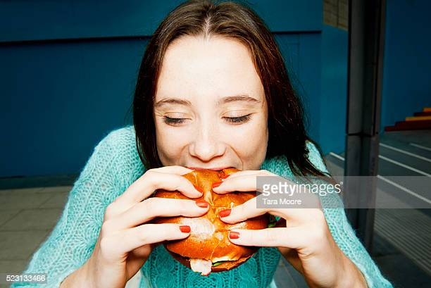 Young woman eating burger