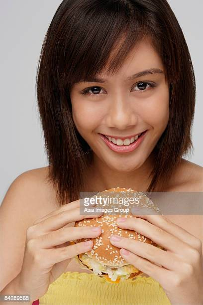 young woman eating burger - strapless stock pictures, royalty-free photos & images