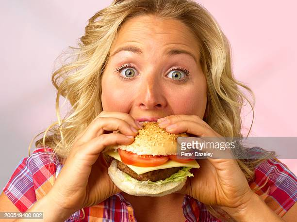 Young woman eating burger, with eyes wide open, close-up, portrait