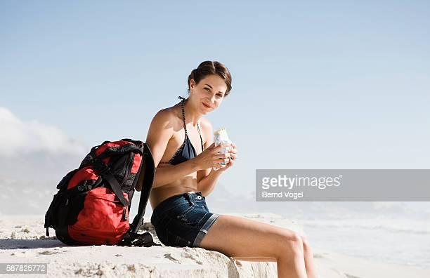 Young Woman Eating Burrito at Beach