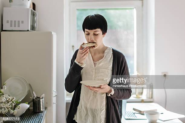 Young Woman Eating Buttered Bread