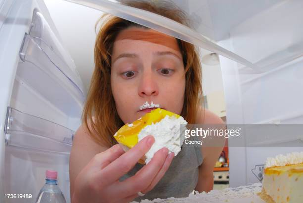 Young woman eating cake in the fridge