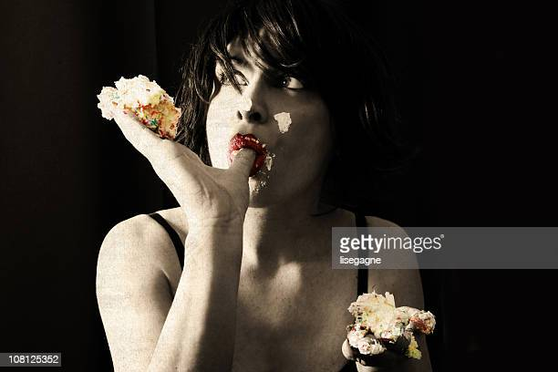 Young Woman Eating Cake with Hands