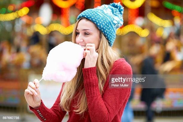 Young woman eating candy floss at funfair, outdoors