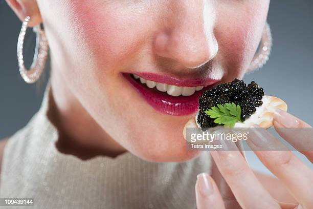 Young woman eating caviar on biscuit