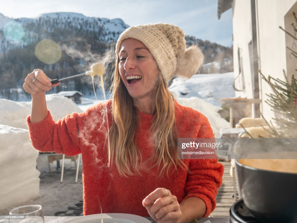 Young woman eating cheese fondue in chalet : Stock Photo