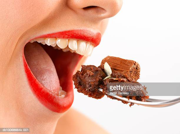 Young woman eating chocolate cake, close up of open mouth, studio shot