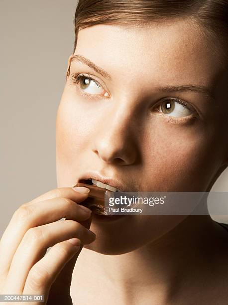 Young woman eating chocolate, looking away, close-up