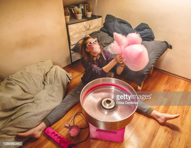 young woman eating cotton candy at home - good; times bad times stock pictures, royalty-free photos & images