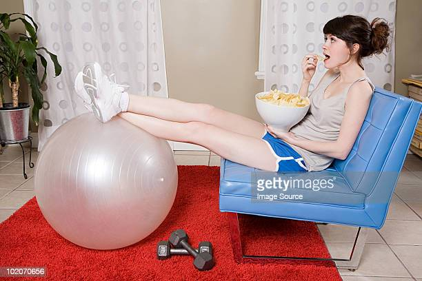 Young woman eating crisps