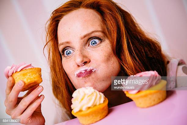 young woman eating cupcakes with a lot of enthusiasm - sweet food stock pictures, royalty-free photos & images