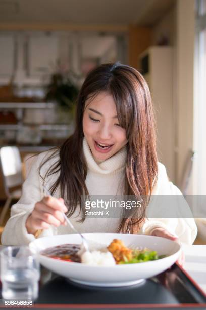 昼食にカレーを食べる若い女性
