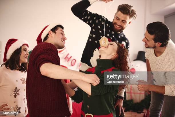 Young woman eating dangled doughnut at christmas party