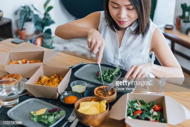 young woman eating delicious takeaway food at home - take away food stock pictures, royalty-free photos & images