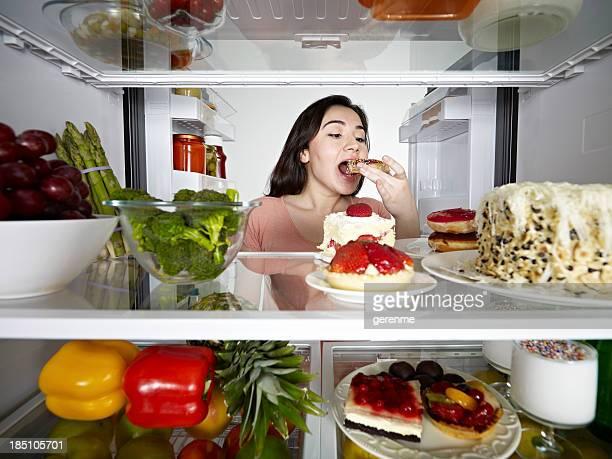 食べるドーナツの若い女性 - いっぱいになる ストックフォトと画像