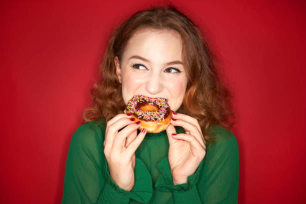 young woman eating donut - 甜品 個照片及圖片檔