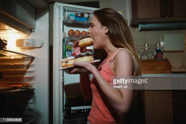 young woman eating doughnuts in the kitchen late night - eating disorder stock pictures, royalty-free photos & images