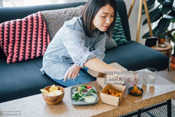 young woman eating fast food at home - take away food stock pictures, royalty-free photos & images