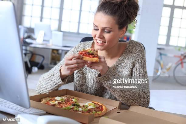 Jeune femme manger Fast-Food au travail