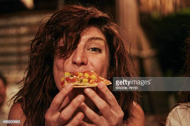 young woman eating food at bar - essen mund benutzen stock-fotos und bilder