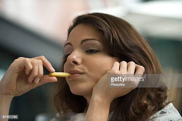 Young woman eating french fries, hand under chin