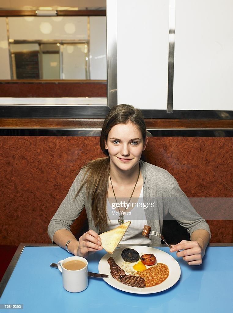 Young woman eating fried breakfast in cafe, portrait : Stock Photo