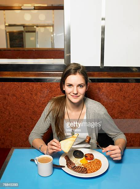 Young woman eating fried breakfast in cafe, portrait
