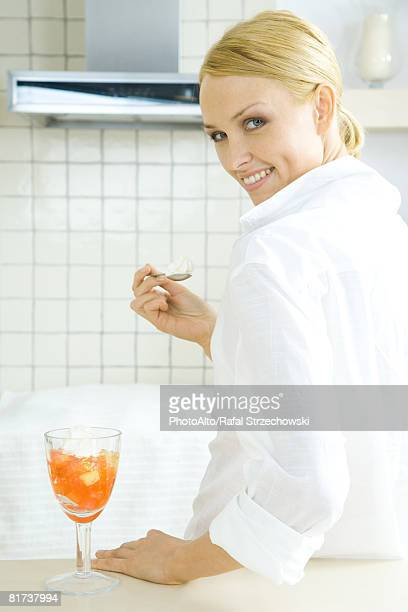 Young woman eating fruit dessert, looking over shoulder at camera