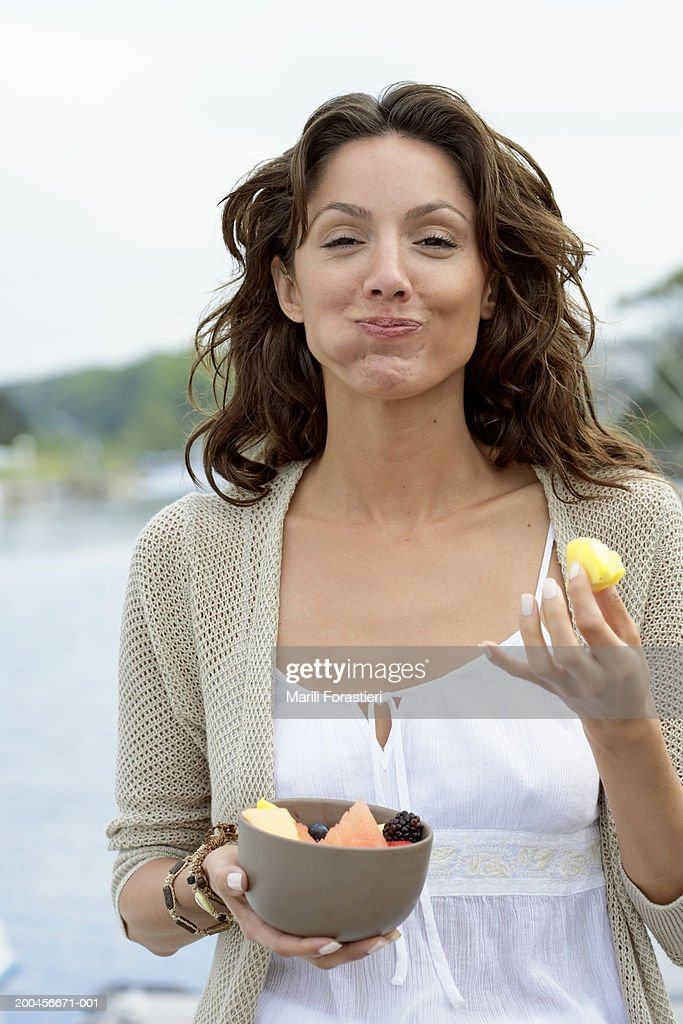 Young woman eating fruit on dock, smiling, portrait, close-up : Stock Photo